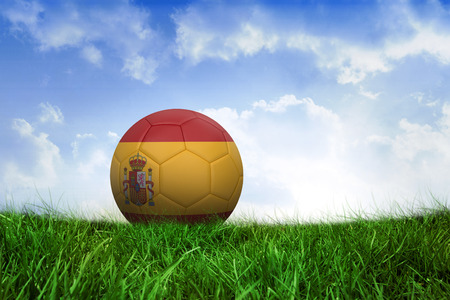 Football in spain colours on field of grass under blue sky photo