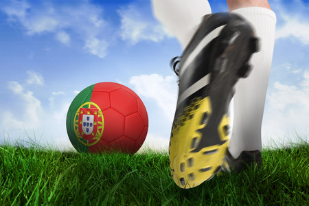 Composite image of football boot kicking portugal ball against field of grass under blue sky photo