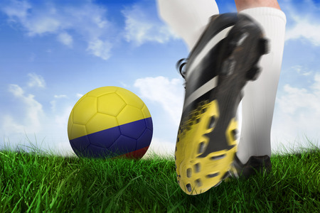 Composite image of football boot kicking colombia ball against field of grass under blue sky