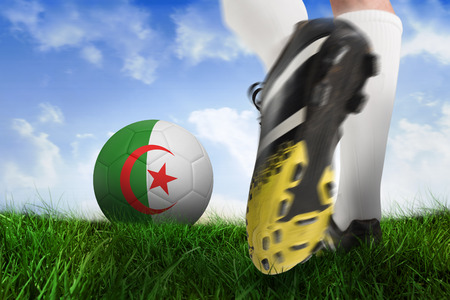 Composite image of football boot kicking iran ball against field of grass under blue sky photo