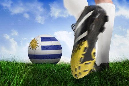Composite image of football boot kicking uruguay ball against field of grass under blue sky photo