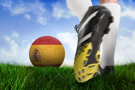 Composite image of football boot kicking spain ball against field of grass under blue sky photo