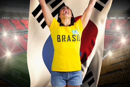 Excited football fan in brasil tshirt against holding south korea flag vast football stadium with fans in yellow and red photo