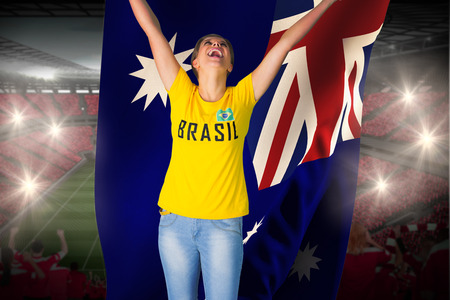 Excited football fan in brasil tshirt holding australia flag against vast football stadium with fans in red photo