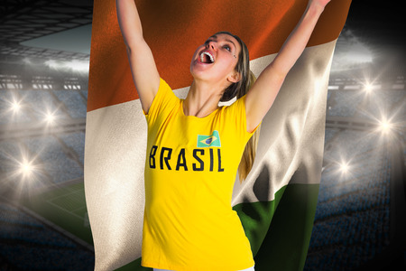 Pretty football fan in brasil t-shirt holding ivory coast flag against large football stadium with fans in blue photo