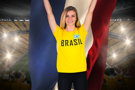Excited football fan in brasil tshirt holding netherlands flag against vast football stadium with fans in yellow photo