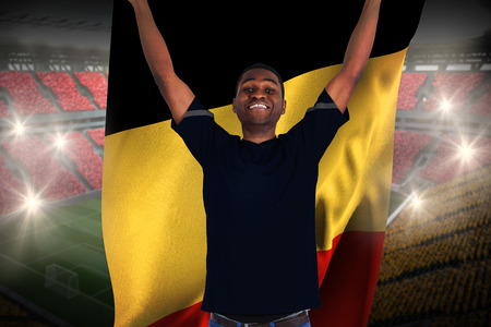 Excited football fan in black cheering holding belgium flag against vast football stadium with fans in yellow and red photo