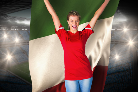Cheering football fan in red against holding italy flag large football stadium with fans in blue photo