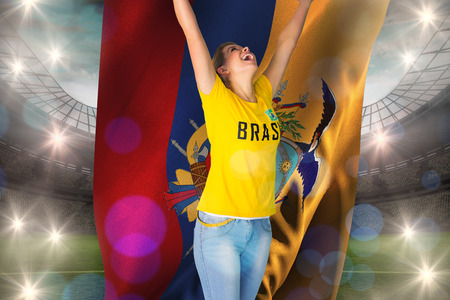Excited football fan in brasil tshirt holding ecudaor flag against large football stadium with lights photo