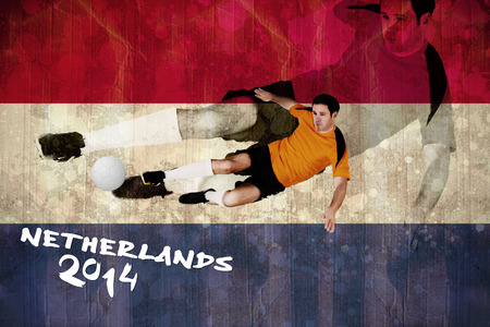 Football player in orange kicking against netherlands flag in grunge effect photo