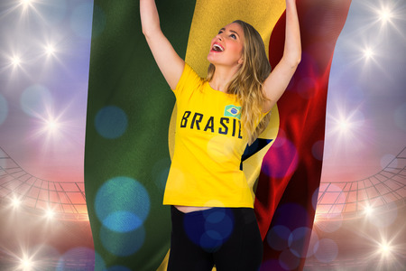Excited football fan in brasil tshirt holding ghana flag against large football stadium under purple sky photo