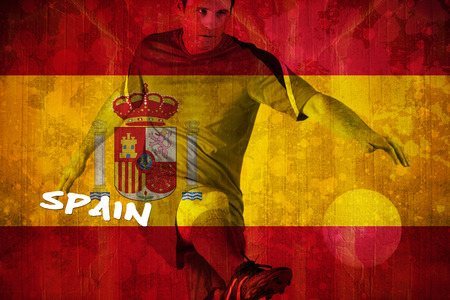 Football player in red kicking against spain flag in grunge effect photo
