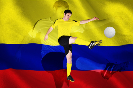 Football player in yellow kicking against digitally generated colombia national flag