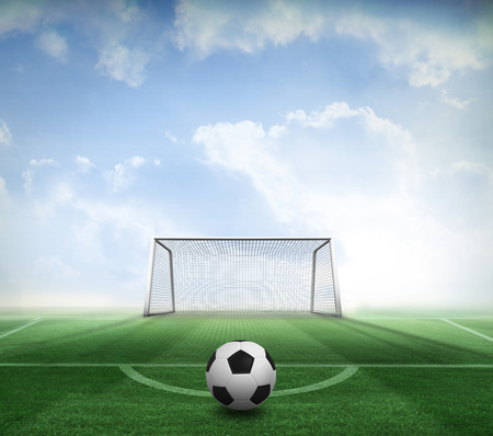 goalpost: Black and white football against football pitch and goal under blue sky