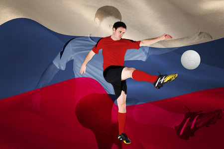 Football player in red kicking against digitally generated russian national flag photo