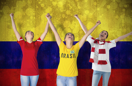 Composite image of various football fans against colombia flag in grunge effect photo