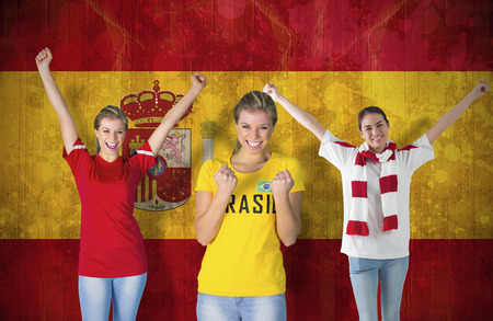 Composite image of various football fans against spain flag in grunge effect photo