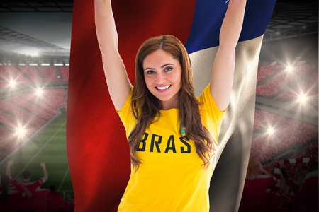 Pretty football fan in brasil t-shirt holding chile flag against vast football stadium with fans in red photo