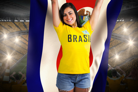 Excited football fan in brasil tshirt holding costa rica flag against vast football stadium with fans in yellow photo