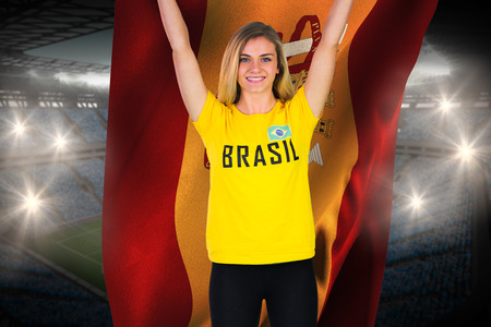 Excited football fan in brasil tshirt holding spain flag against large football stadium with fans in blue photo