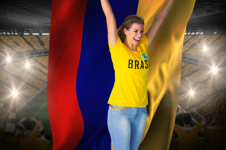 Excited football fan in brasil tshirt holding colombia flag against vast football stadium with fans in yellow photo