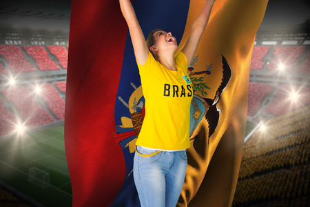 Excited football fan in brasil tshirt holding ecuador flag against vast football stadium with fans in yellow and red photo