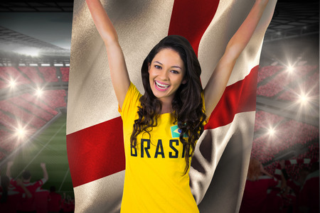 Excited football fan in brasil tshirt holding england flag against vast football stadium with fans in red photo