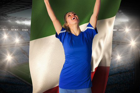 Cheering football fan in blue jersey holding italy flag against large football stadium with fans in blue photo