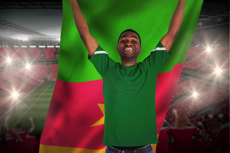 Cheering football fan in green jersey holding cameroon flag against vast football stadium with fans in red photo