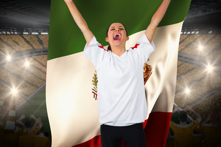 Football fan in white cheering holding mexico flag against vast football stadium with fans in yellow