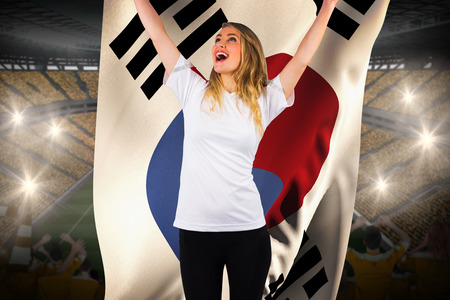 Pretty football fan in white cheering holding south korea flag against vast football stadium with fans in yellow photo