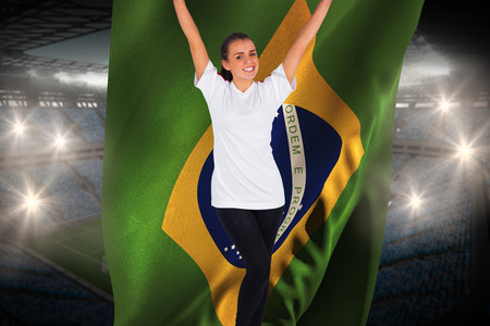 Excited football fan in white cheering holding brasil flag against large football stadium with fans in blue photo