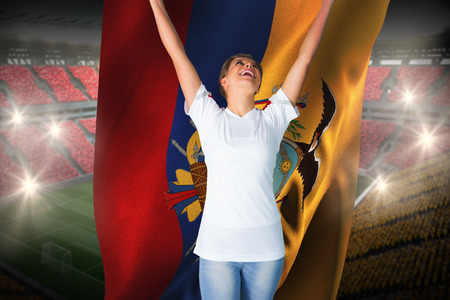 Pretty football fan in white cheering holding ecuador flag against vast football stadium with fans in yellow and red photo