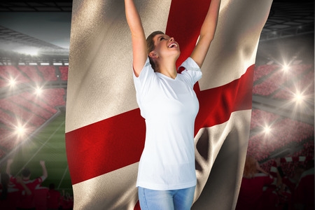 Pretty football fan in white cheering holding england flag against vast football stadium with fans in red photo
