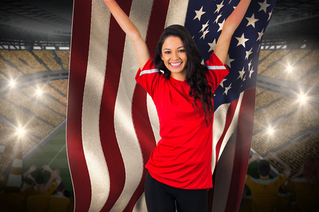Cheering football fan in red holding usa flag against vast football stadium with fans in yellow photo