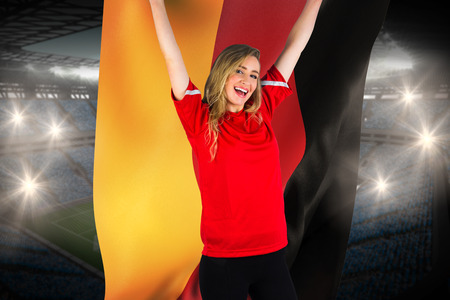 Cheering football fan in red holding germany flag against large football stadium with fans in blue photo