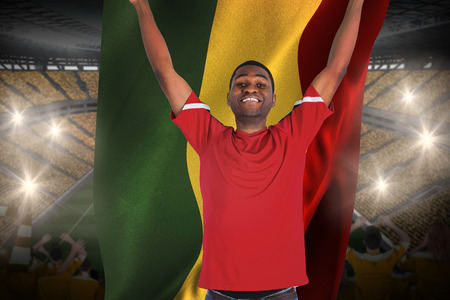 Excited handsome football fan cheering holding ghana flag against vast football stadium with fans in yellow photo