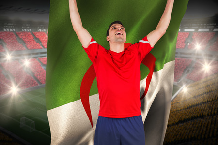 Excited football player cheering holding algeria flag against vast football stadium with fans in yellow and red photo