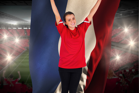 Excited football fan in red cheering holding france flag against vast football stadium with fans in red photo