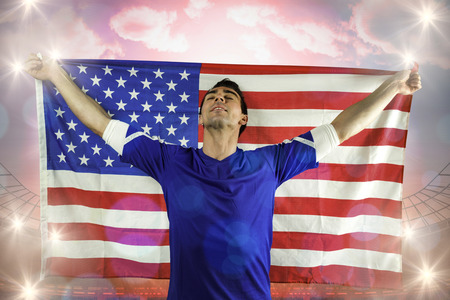 American soccer fan holding flag against large football stadium under bright blue sky photo