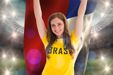 Pretty football fan in brasil t-shirt holding chile flag against large football stadium with lights photo