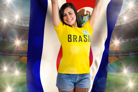 Excited football fan in brasil tshirt holding costa rica flag against large football stadium with brasilian fans photo