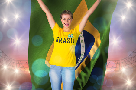 Excited football fan in brasil tshirt holding brasil flag against large football stadium under purple sky photo