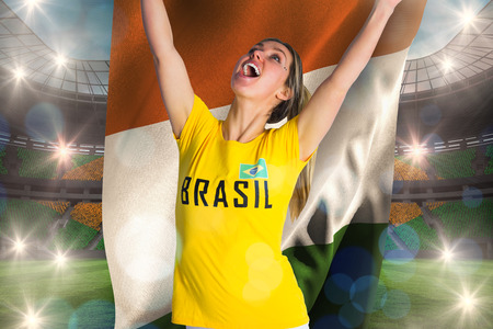 Pretty football fan in brasil t-shirt holding ivory coast flag against large football stadium with brasilian fans photo