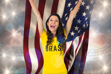 Excited football fan in brasil tshirt holding usa flag against large football stadium under cloudy blue sky photo