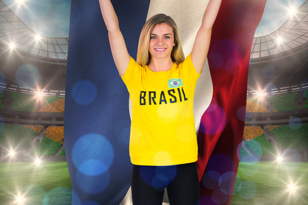 Excited football fan in brasil tshirt holding netherlands flag against large football stadium with brasilian fans photo