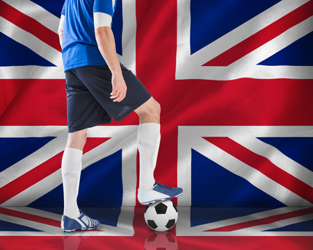 Football player in blue jersey against digitally generated uk national flag photo