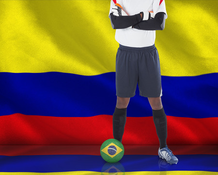 Composite image of goalkeeper in white with ball against digitally generated colombia national flag photo