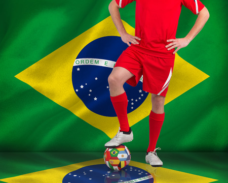 Composite image of football player standing with ball against digitally generated brazilian national flag photo