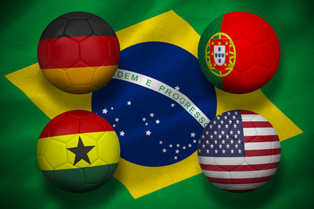 Composite image of group g footballs for world cup against digitally generated brazilian national flag photo